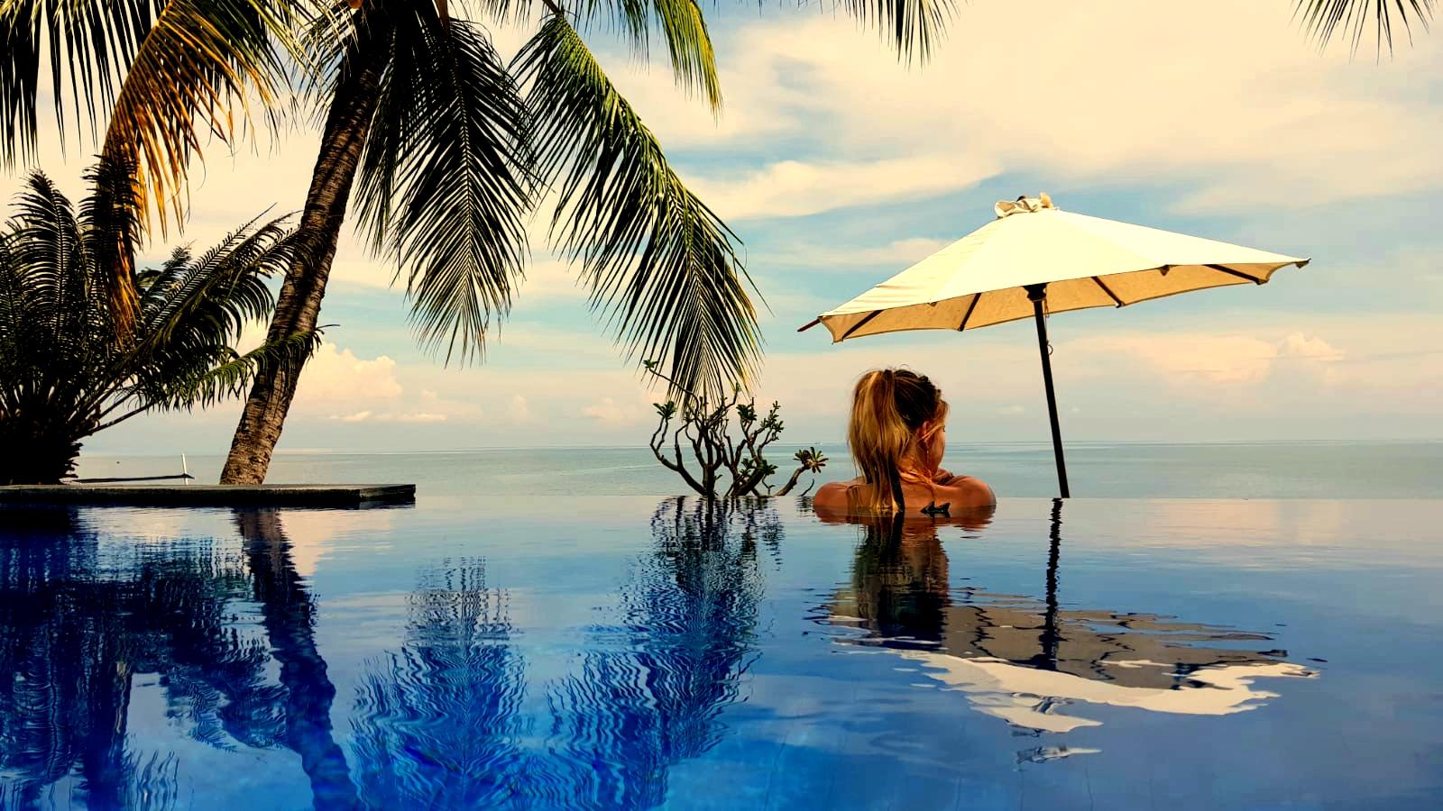 Kracht van kleur - Katrín kijkt vanuit zwembad over de turquoise zee van Bali